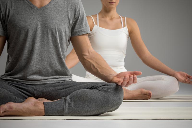 Young sporty woman practicing yoga, Prasarita Navasana pose